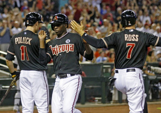 Arizona Diamondbacks Didi Gregorius (1), middle, celebrates with A.J. Pollock (11), and Cody Ross (7) after all of them score on a Wade Miley double in the second inning during a baseball game against the Colorado Rockies on Saturday, July 6, 2013, in Phoenix. (AP Photo/Rick Scuteri)