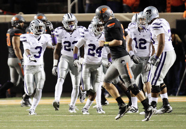 The Kansas State Wildcats celebrate an interception returned for a touchdown as OSU quarterback Brandon Weeden returns to the sideline in the second quarter during a college football game between the Oklahoma State University Cowboys (OSU) and the Kansas State University Wildcats (KSU) at Boone Pickens Stadium in Stillwater, Okla., Saturday, Nov. 5, 2011.  Photo by Nate Billings, The Oklahoman