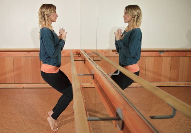 Andrea Mason, owner of Barre3, demonstrates Power Leg. Start standing tall with feet hip distance apart. Roll onto the balls of your feet and bend your knees while keeping your shoulders over your hips. Ankles, hips, shoulders and ears are all aligned. Targets the quadriceps. Photo by Chris Landsberger, The Oklahoman. <strong>CHRIS LANDSBERGER</strong>