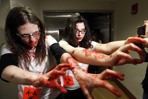 "Students Shara Evans, of West Bloomfield, Mich., left, and Maia Frieser, of New York, act during a ""zombie apocalypse"" exercise, which included students dressing up as the undead, in Ann Arbor, Mich. Tuesday April 23, 2013. The exercise was designed to get School of Public Health students thinking about what the appropriate response should be during a disaster. (AP Photo/Paul Sancya)"
