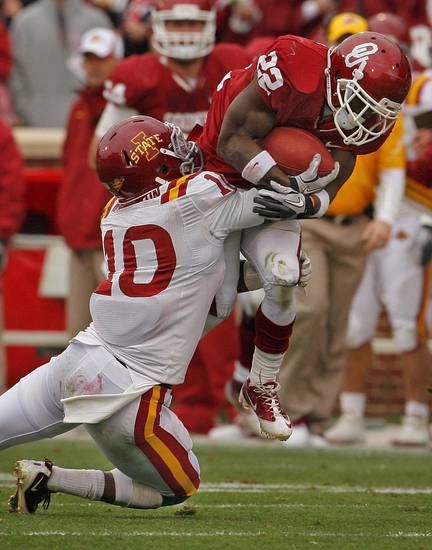 Oklahoma's Roy Finch (22) leaps to try and avoid the tackle of Iowa State's Jacques Washington (10) during the second half of a college football game in which  the University of Oklahoma Sooners (OU) defeated the Iowa State University Cyclones (ISU) 26-6 at Gaylord Family-Oklahoma Memorial Stadium in Norman, Okla., Saturday, Nov. 26, 2011. Photo by Steve Sinsey, The Oklahoman