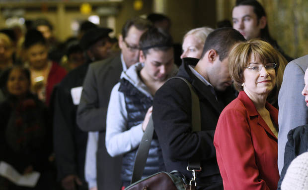 U.S. Senator Amy Klobuchar, D Minn., right, stands in line waiting to vote at Marcy School, Tuesday, Nov. 6, 2012 in Minneapolis. (AP Photo/Andy King)