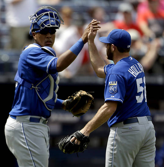 Kansas City Royals relief pitcher Greg Holland, right, high-fives teammate Salvador Perez after the Royals beat the Atlanta Braves 1-0 in a baseball game, Wednesday, April 17, 2013, in Atlanta. (AP Photo/David Goldman)
