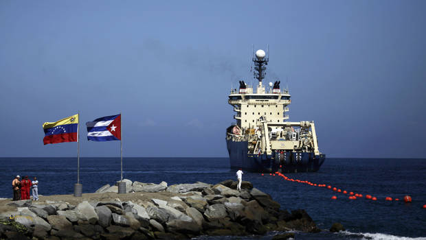 FILE - In this Jan. 22, 2011 file photo, people stand on a breakwater, with a Venezuelan flag, left, and a Cuban flag, as a specialized ship rolls out a fiber-optic cable, suspended from buoys, off La Guaira, Venezuelan coast. Cuba&#039;s state telecom monopoly confirmed Thursday, Jan. 24, 2013 that the island&#039;s first hard-wired Internet connection to the outside world has been activated, but said it won&#039;t lead to an immediate increase in access. The $70 million ALBA-1 arrived on the island from Venezuela in February 2011 to great hoopla, but officials soon stopped mentioning the cable amid rumors of mismanagement and corruption involving the project.  (AP Photo/Ariana Cubillos, File)