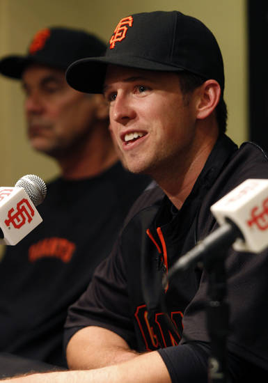 San Francisco Giants' Buster Posey smiles at a news conference, Friday, March 29, 2013 in San Francisco. The Giants and Posey have reached an agreement on a new nine year contract through 2021 with an option for the 2022 season. Giants manager Bruce Bochy is in the background. (AP Photo/George Nikitin)