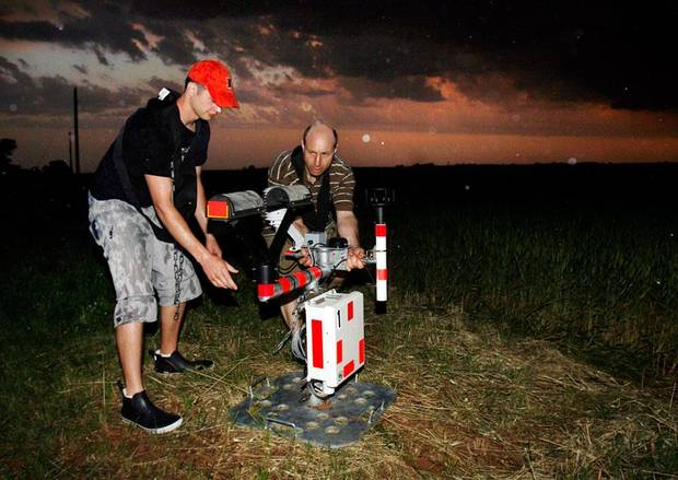Isaac Hankes and research scientist Glen Romine from the University of Illinois deploy a laser distrometer to measure particle size, rate, and direction (raindrops) as members of VORTEX2 track an emerging super cell in central Oklahoma on Wednesday, May 13, 2009.  Photo by Steve Sisney, The Oklahoman