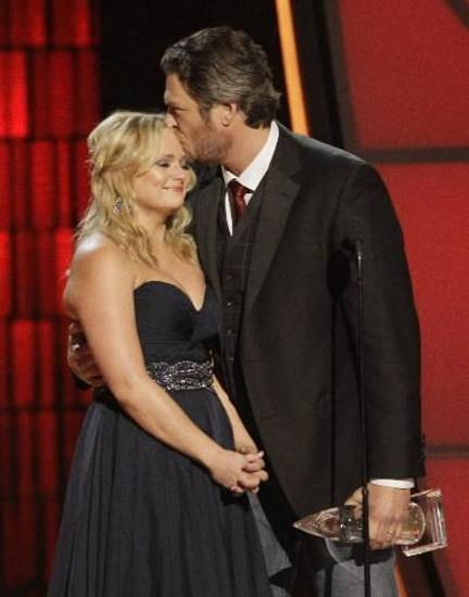 Shelton kisses his wife as they accept the song of the year award.