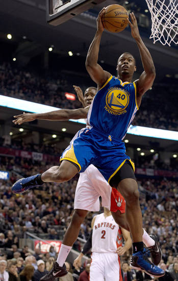 Golden State Warriors forward Harrison Barnes (40) drives to the basket ahead of Toronto Raptors forward Ed Davis during the first half of their NBA basketball game, Monday, Jan. 28, 2013, in Toronto. (AP Photo/The Canadian Press, Frank Gunn)