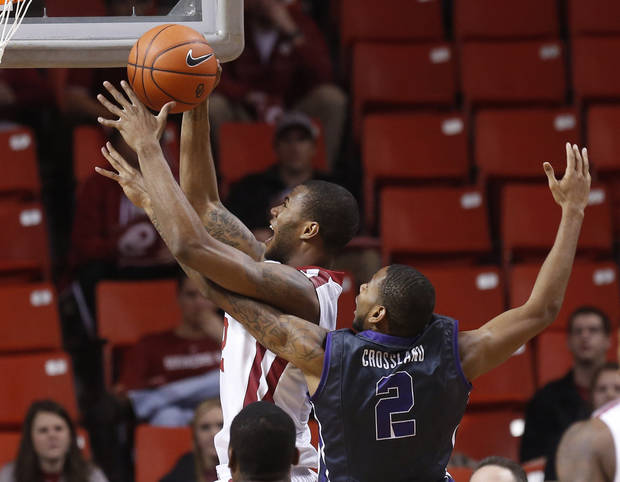 Oklahoma forward Amath M'Baye (22) shoots in front of TCU forward Connell Crossland (2) in the first half of an NCAA college basketball game in Norman, Okla., Monday, Feb. 11, 2013. (AP Photo/Sue Ogrocki)