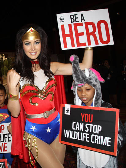 Miss Universe 2005 Natalie Glebova of Canada, wearing Wonder Woman costume poses with Thai children during Convention on International Trade in Endangered Species, or CITES, in Bangkok, Thailand Sunday, March 3, 2013. How to slow the slaughter and curb the trade in &quot;blood ivory&quot; will be among the most critical issues up for debate at the 177-nation Convention on International Trade in Endangered Species, or CITES, that gets under way Sunday in Bangkok. And the meeting&#039;s host, Thailand, will be under particular pressure to take action. (AP Photo/Sakchai Lalit)