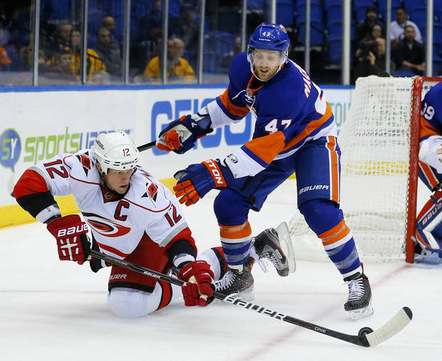 Carolina Hurricanes center Eric Staal (12) passes the puck out to a teammate in front of New York Islanders&#039; Andrew MacDonald (47) during the first period of an NHL hockey game at the Nassau Coliseum in Uniondale, N.Y., Monday, Feb.11, 2013. (AP Photo/Paul J. Bereswill)