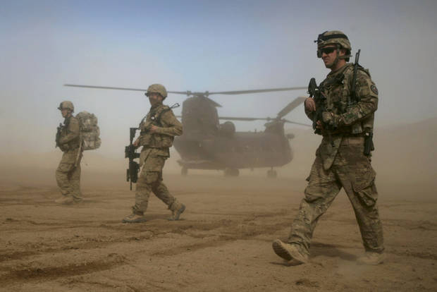 FILE - In this Saturday, Jan. 28, 2012 file photo, U.S. soldiers, part of the NATO- led International Security Assistance Force (ISAF) walks, as a U.S. Chinook helicopter is seen on the back ground near the place where the foundation of a hospital was laid in Shindand, Herat, west of Kabul, Afghanistan. The phrases to describe some of the looming foreign policy challenges for U.S. President Barack Obama didn't even exist when he took the oath of office the first time: the Arab Spring, the Fordo Facility housing Iran's underground uranium enrichment labs, the stealth power of new viruses bearing names such as Stuxnet and Flame in the shadow world of cyber-sabotage. While the war in Afghanistan, now in its 12th year, was barely a topic on the campaign trail, the country will certainly command a great deal of Obama's attention in his second term. Obama soon will receive his top military officials' recommendations about how fast to withdraw the roughly 66,000 U.S. troops still in Afghanistan. The first 33,000 American troops withdrew by the end of September.(AP Photo/Hoshang Hashimi, File)