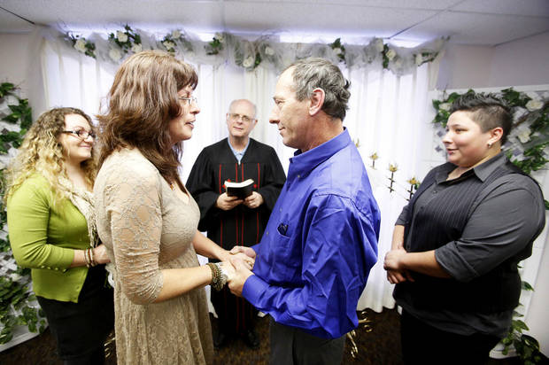 Jerry Freeland, center, officiates the wedding of Tammie and Roger Lockwood at the Courthouse Lab and Wedding Chapel in Oklahoma City. Witnessing the 12-12-12 wedding are Hannah Allen, left and Krystle Zepeda.  Photo By Steve Gooch, The Oklahoman