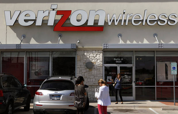 FILE - In this Wednesday, Oct. 17, 2012, file photo, customers walk into a Verizon Wireless store in Dallas. A federal appeals court rejected a Verizon challenge to a Federal Communications Commission rule aimed at increasing competition in wireless broadband service. on Tuesday, Dec. 4, 2012. (AP Photo/LM Otero, File)