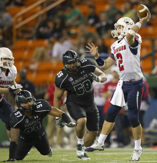 Hawaii defensive lineman Tavita Woodard (97) and defensive lineman Siasau Matagiese (59) rush South Alabama quarterback Ross Metheny (2) in the third quarter of an NCAA college football game Saturday, Dec. 1, 2012, in Honolulu. (AP Photo/Eugene Tanner)