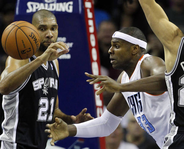 Charlotte Bobcats&#039; Brendan Haywood (33) and San Antonio Spurs&#039; Tim Duncan (21) battle for a rebound during the first half of an NBA basketball game in Charlotte, N.C., Saturday, Dec. 8, 2012. (AP Photo/Chuck Burton)