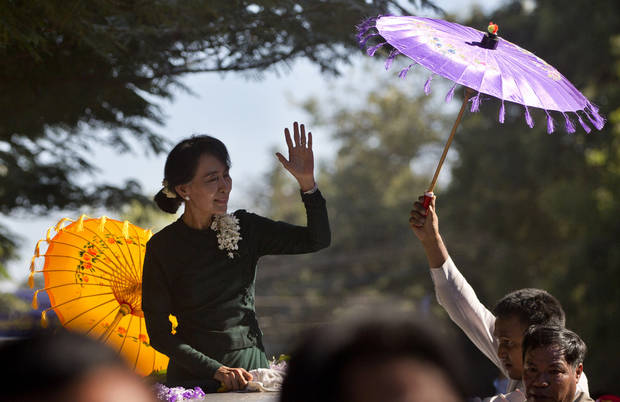 Opposition leader Aung San Suu Kyi waves to her supporters as she arrives in Monywa town, northwestern Myanmar, Thursday, Nov. 29, 2012. Security forces used water cannons, tear gas and smoke bombs Thursday to clear protesters from a copper mine in northwestern Myanmar, wounding villagers and Buddhist monks just hours before Suu Kyi arrived in the area to hear their grievances. (AP Photo/Gemunu Amarasinghe)