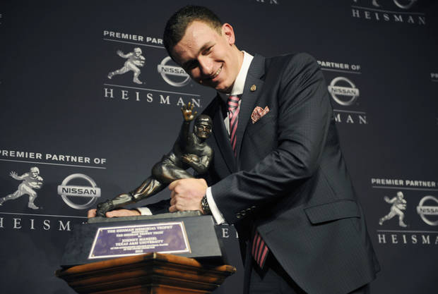 Texas A&M quarterback Johnny Manziel poses with the Heisman Trophy after becoming the first freshman to win the award, Saturday, Dec. 8, 2012, in New York. (AP Photo/Henny Ray Abrams) ORG XMIT: NYHA113