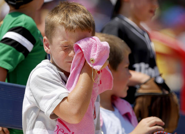 Wyatt Cargill, 6, of Edmond wipes sweat off his face during a World Cup of Softball game between USA and the Netherlands at ASA Hall of Fame Stadium in Oklahoma City, Saturday, June 30, 2012. Photo by Bryan Terry, The Oklahoman