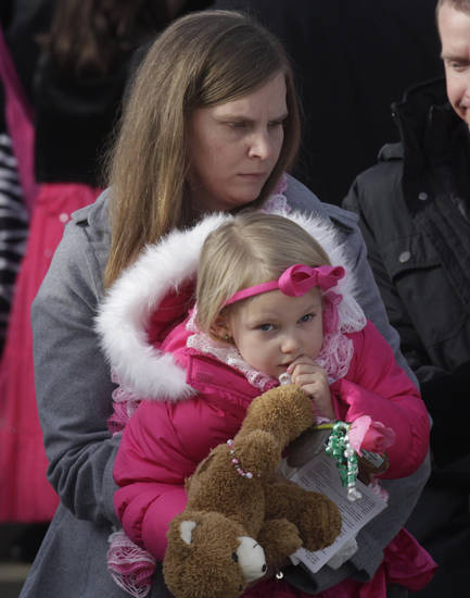 Alissa Parker carries her daughter following funeral services for her daughter, Connecticut elementary shooting victim Emilie Parker, Saturday, Dec. 22, 2012, at the Church of Jesus Christ of Latter -Day, in Ogden, Utah. Emilie, whose family has Ogden roots, was one of 20 children and six adult victims killed in a Dec. 14 mass shooting at Sandy Hook Elementary in Newtown, Conn. (AP Photo/Rick Bowmer)
