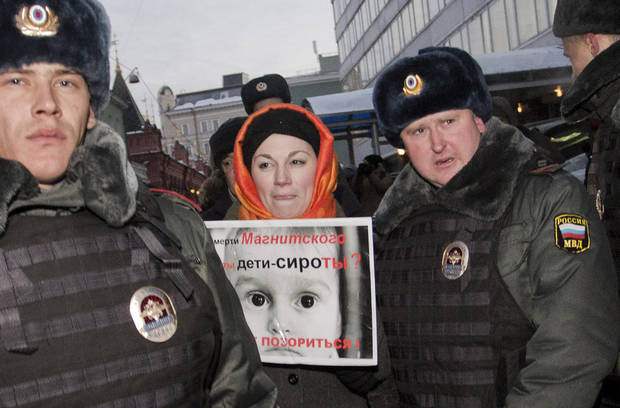 Police officers detain a protester near the State Duma, in Moscow, Russia, Wednesday, Dec. 19, 2012. People picket parliament&#039;s lower chamber, to protest against planned debate of an amendment that would ban Americans from adopting Russian children. The poster reads: Are orphans guilty of Magnitsky&#039;s death ? Stop putting shame on yourselves! Sergei Magnitsky, a Russian lawyer who was arrested by the officials he accused of a $230 million tax fraud. He was repeatedly denied medical treatment and in 2009 died in jail. (AP Photo/Novaya Gazeta, Yevgeny Feldman)
