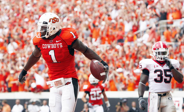 Oklahoma State's Dez Bryant, left, celebrates  in front of Georgia's Rennie Curran after scoring a touchdown during Saturday's win over the Bulldogs at Boone Pickens Stadium. Photo by Sarah Phipps, The Oklahoman