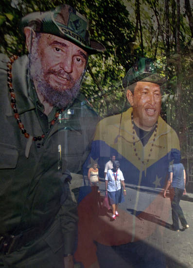 Pedestrians are reflected in a framed image of Cuba's Fidel Castro, left, and Venezuela's President Hugo Chavez, hanging inside a shop, in Havana, Cuba, Friday, Jan. 4, 2013. Chavez hasn't spoken publicly or been seen since his Dec. 11 operation in Cuba, and the latest report from his government Thursday night increased speculation that he is unlikely to attend his Jan. 10 inaugural ceremony. (AP Photo/Ramon Espinosa)