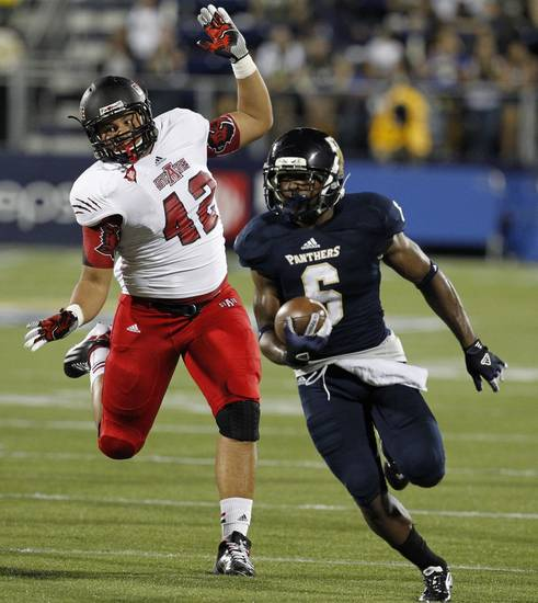 Florida International's Jeremiah Harden, right, moves the ball in the red zone to help set up an FIU field goal as Arkansas State University's Chris Stone pursues in the second quarter of an NCAA college football game at FIU Stadium in Miami, Thursday, Oct. 4, 2012. (AP Photo/The Miami Herald, Charles Trainor Jr.) MAGAZINES OUT