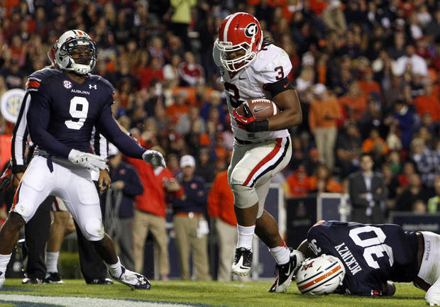 Georgia running back Todd Gurley (3) carries the ball over Auburn linebacker Cassanova McKinzy (30) for a touchdown during the first half of an NCAA college football game on Saturday, Nov. 10, 2012, in Auburn, Ala. (AP Photo/Butch Dill)