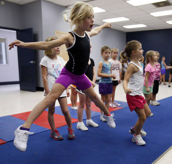 Ella Hodges, 7, practices leaps at a city-sponsored cheer and tumbling camp on Wednesday, July 18, 2012 in Norman, Okla.     Photo by Steve Sisney, The Oklahoman