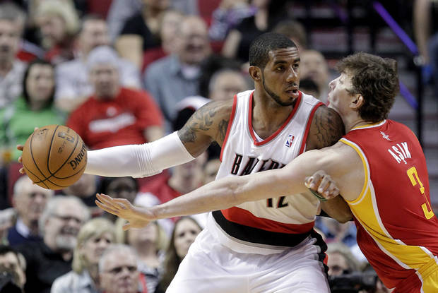 Houston Rockets center Omer Asik, right, from Turkey, reaches in on Portland Trail Blazers forward LaMarcus Aldridge during the first quarter of an NBA basketball game in Portland, Ore., Friday, April 5, 2013.(AP Photo/Don Ryan)