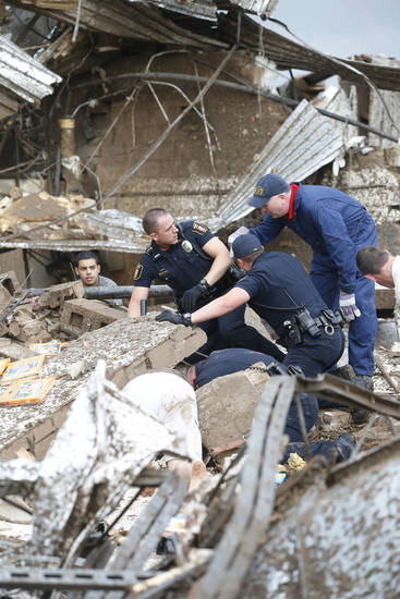 Rescue workers dig through the rubble of a collapsed wall at the Plaza Tower Elementary School to free trapped students in Moore, Okla., following a tornado Monday, May 20, 2013. (AP Photo Sue Ogrocki) ORG XMIT: OKSO125