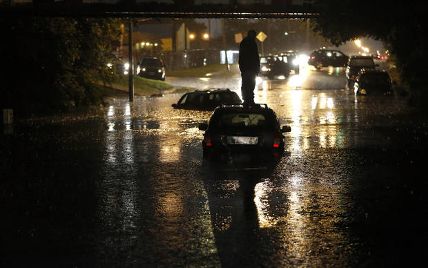 A man stands on top of his car as it is flooded on S. May Ave near SW 25th in Oklahoma City, Friday, May 31, 2013. Photo by Sarah Phipps, The Oklahoman.