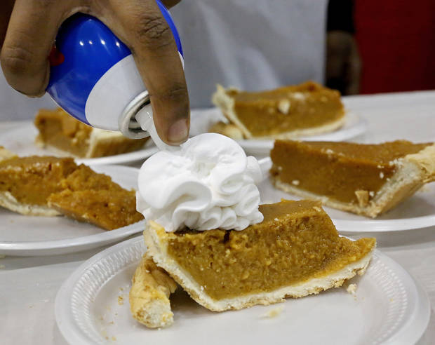 A volunteer piles whipped topping on a piece of pumpkin pie. Hundreds were served a traditional Christmas meal at the annual Red Andrews Dinner inside the Cox Convention Center on Christmas Day, Dec. 25, 2012. An army of  volunteers showed up despite  snow and ice and hazardous driving conditions. They accompanied each guest through the serving line and carried their trays and seated them at their tables. Other volunteers distributed a small mountain of toys and stuffed animals that were donated for the event.   Photo by Jim Beckel, The Oklahoman <strong>Jim Beckel - THE OKLAHOMAN</strong>