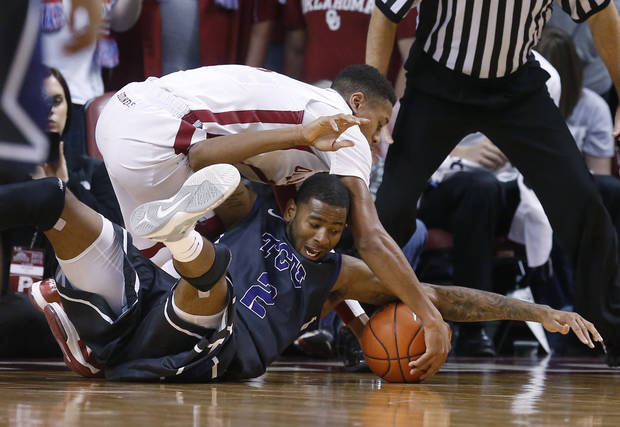 Oklahoma guard Isaiah Cousins, top, and TCU forward Connell Crossland (2) fight for control of a loose ball in the second half of an NCAA college basketball game in Norman, Okla., Monday, Feb. 11, 2013. Oklahoma won 75-48. (AP Photo/Sue Ogrocki)