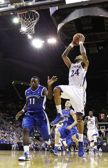 Kansas guard Travis Releford (24) shoots past Saint Louis guard Mike McCall Jr., (11) during the first half of an NCAA college basketball game, Tuesday, Nov. 20, 2012, in Kansas City, Mo. (AP Photo/Charlie Riedel)