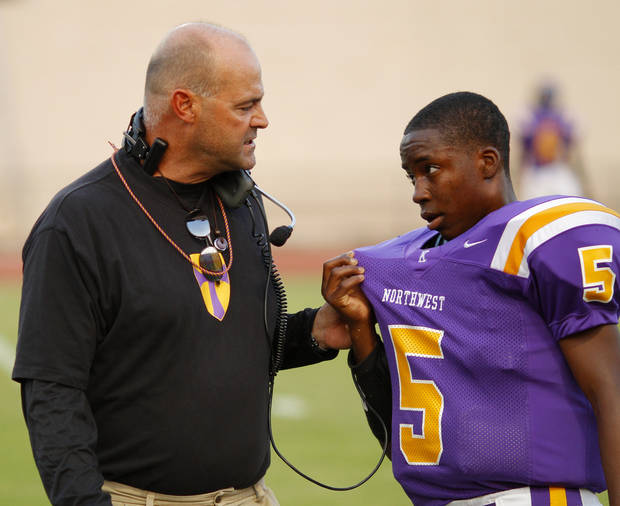 NWC Coach Smith talks with Jimmy Reece (5) as he comes off the field while Jimmy wipes sweat from his face with his jersey at the Northwest Classen vs. Western Heights high school football game at Taft Stadium Thursday, September 20, 2012. Photo by Doug Hoke, The Oklahoman