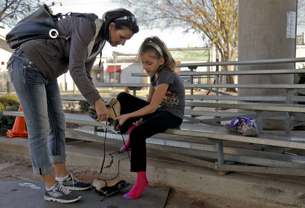Nicole McFarlane helps her daughter Halle put on her ice skates at the Edmond outdoor ice skating rink on Sunday, Dec. 2, 2012, in Edmond, Okla.   Photo by Chris Landsberger, The Oklahoman