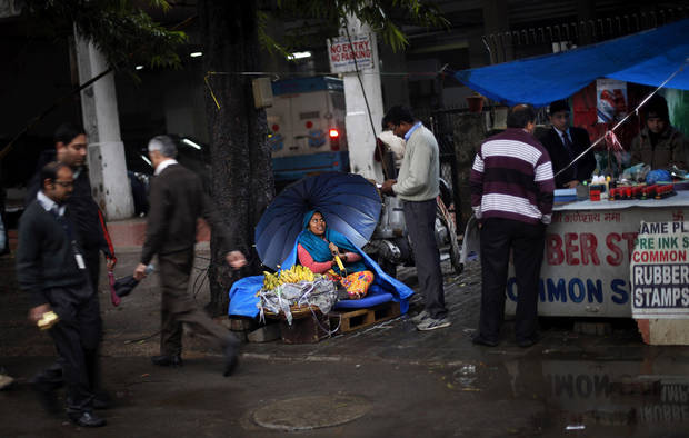 An Indian roadside banana vendor holds an umbrella as she talks to a customer while it rains in New Delhi, India, Tuesday, Feb. 5, 2013. Heavy rains accompanied by a thunderstorm lashed the capital for the second day Tuesday throwing traffic out of gear across the city. (AP Photo/Altaf Qadri)