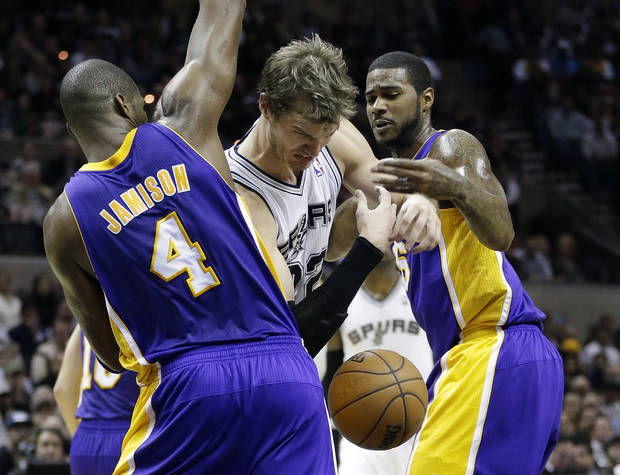 San Antonio Spurs' Tiago Splitter, center, of Brazil, loses control of the ball as Los Angeles Lakers' Antawn Jamison (4) and Earl Clark, right, defend during the first quarter of an NBA basketball game on Wednesday, Jan. 9, 2013, in San Antonio. (AP Photo/Eric Gay)