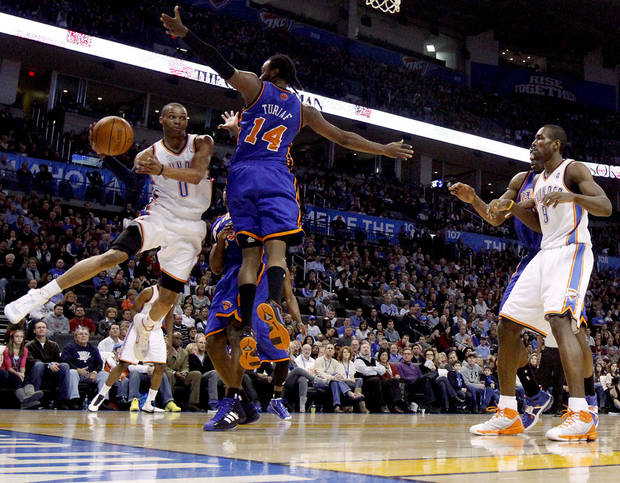 Oklahoma City's Russell Westbrook passes the ball around New York's Ronny Turiaf during the NBA basketball game between the Oklahoma City Thunder and the New York Knicks at the Oklahoma City Arena in Oklahoma City on Saturday, January 22, 2011.  Photo by Bryan Terry, The Oklahoman ORG XMIT: KOD