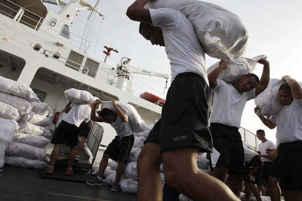 Members of the Philippine Coast Guard carry relief goods for victims of flash floods caused by Typhoon Bopha in Davao province while loading their ship in Manila, Philippines on Thursday, Dec. 6, 2012. The powerful typhoon that washed away emergency shelters, a military camp and possibly entire families in the southern Philippines has killed hundreds of people with nearly 400 missing, authorities said Thursday. (AP Photo/Aaron Favila)