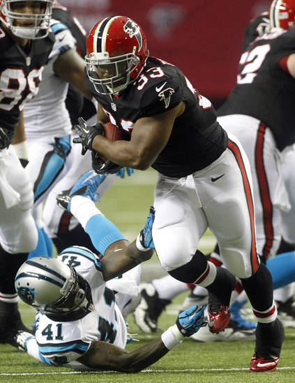 Atlanta Falcons running back Michael Turner (33) runs out of the tackle of Carolina Panthers cornerback Captain Munnerlyn (41)during the first half of an NFL football game Sunday, Sept. 30, 2012, in Atlanta. (AP Photo/John Bazemore)