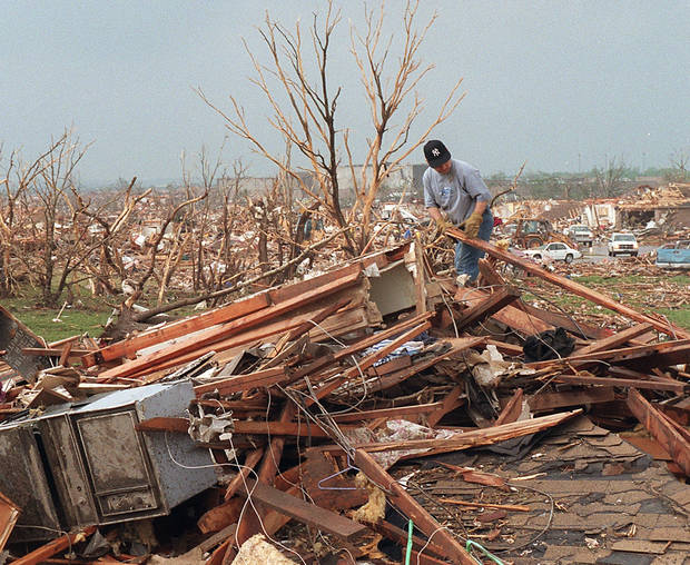 MAY 3, 1999 TORNADO: Tornado victims: Bill Paige sorts through tornado damage in Moore off Western and 12th street.  Westmoore High School is in the background.