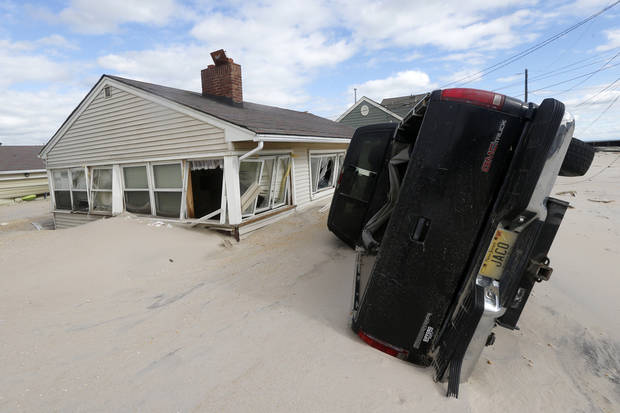 Sand from the beach is seen up to the windows of a home as a vehicle sits on its side following superstorm Sandy, Wednesday, Oct. 31, 2012, in Seaside Heights, N.J. (AP Photo/Julio Cortez) ORG XMIT: NJJC110