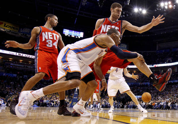 Oklahoma City's Russell Westbrook passes the ball around New Jersey's Devin Harris, left, and Brook Lopez during the NBA basketball game between the Oklahoma City Thunder and the New Jersey Nets at the Oklahoma City Arena, Wednesday, Dec. 29, 2010.  Photo by Bryan Terry, The Oklahoman ORG XMIT: KOD