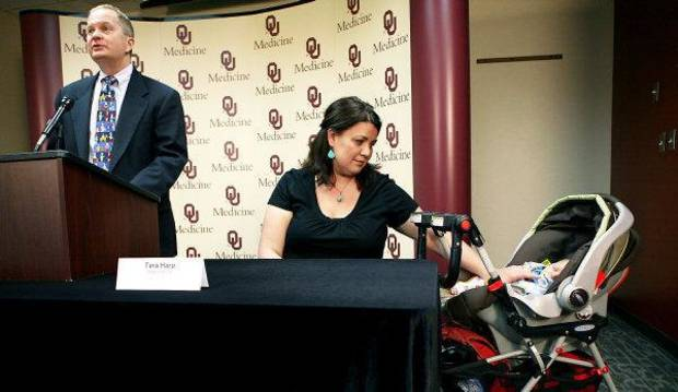 Tara Harp and her 3-month-old son Elijah wait while Dr. Michael Siatkowski speaks during a press conference. <strong>John Clanton</strong>