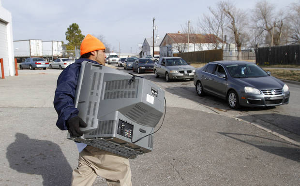 Julio De'Lagarza carries a TV to a waiting car at the Jesus House in Oklahoma City, Monday December 24, 2012. Photo By Steve Gooch, The Oklahoman