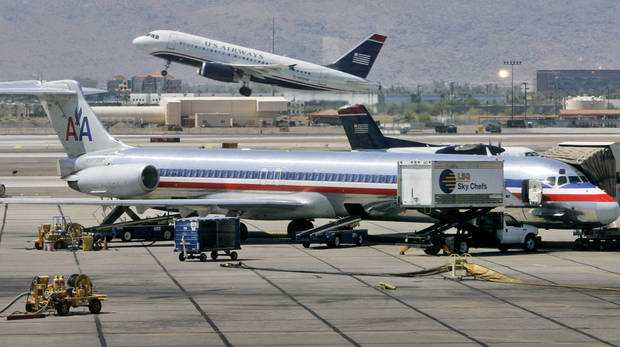 FILE - In this June 23, 2008 file photo, a US Airways jet takes off as an American Airlines jet is prepped for takeoff at Sky Harbor International Airport in Phoenix. The merger of US Airways and American Airlines has given birth to a mega airline with more passengers than any other in the world. (AP Photo/Matt York, File)