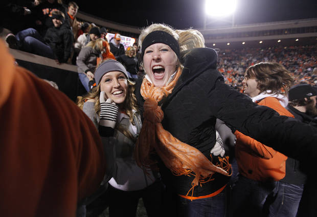 Fans storm the field to celebrate the Cowboys' 44-10 win over Oklahoma during the Bedlam college football game between the Oklahoma State University Cowboys (OSU) and the University of Oklahoma Sooners (OU) at Boone Pickens Stadium in Stillwater, Okla., Saturday, Dec. 3, 2011. Photo by Chris Landsberger, The Oklahoman